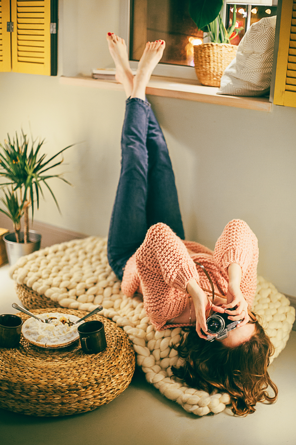 photographer woman quirky shot photo techology crossed legs jeans knitted jumper house home rug interior design