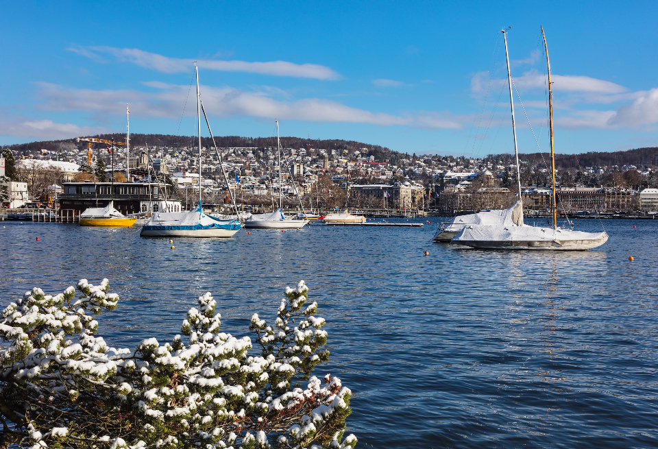 Zurich Switzerland view city Zurich Lake Zurich lakeside snow white winter wintertime hill building water buoy boat sailboat yacht lake pier skyline cityscape sky blue cloud Swiss Europe European