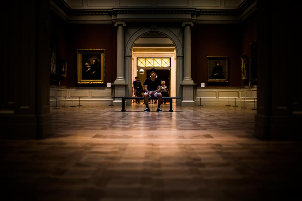 people man sitting alone museum building establishment painting dark night