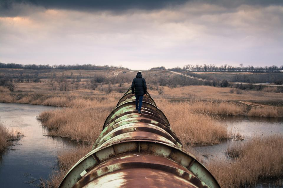 pipe pipeline people man guy walking rural river water reeds grass fields cloudy clouds sky