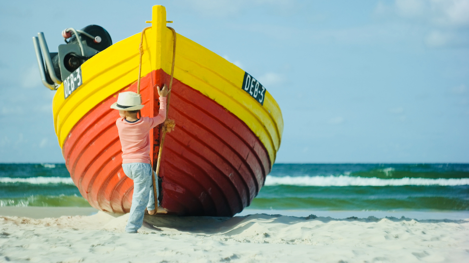boy fishing boat red yellow sand beach ocean water sea blue sky toddler male family