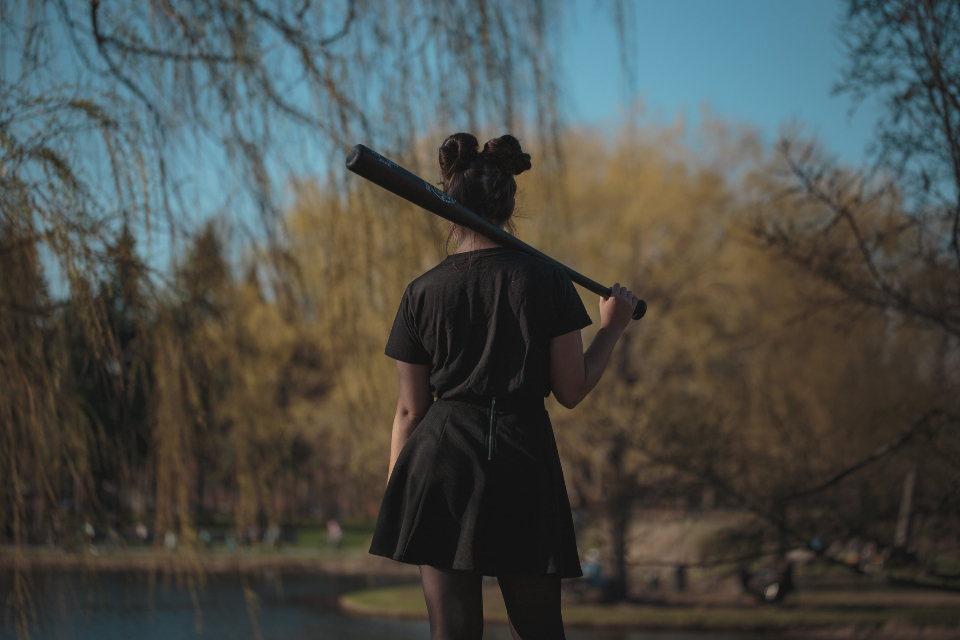 woman baseball bat outdoors nature trees spooky mysterious dangerous female person standing tough lady youth athlete