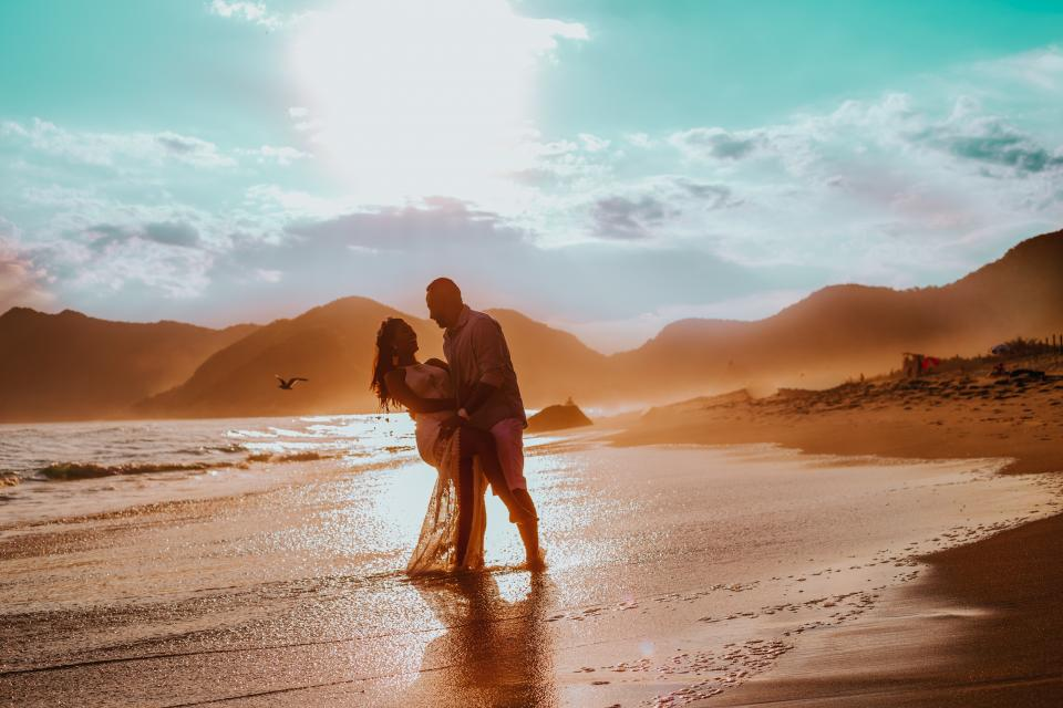 sea ocean water wave nature beach shore sunlight mountain landscape sky cloud people couple man woman hug smile happy