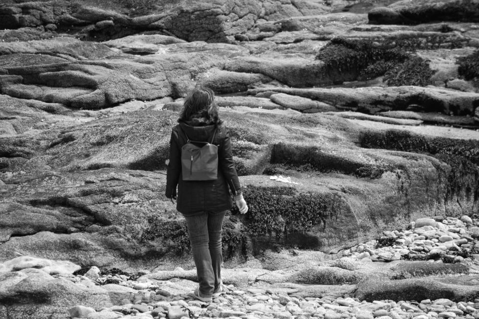black and white people girl walking alone coast rock stone