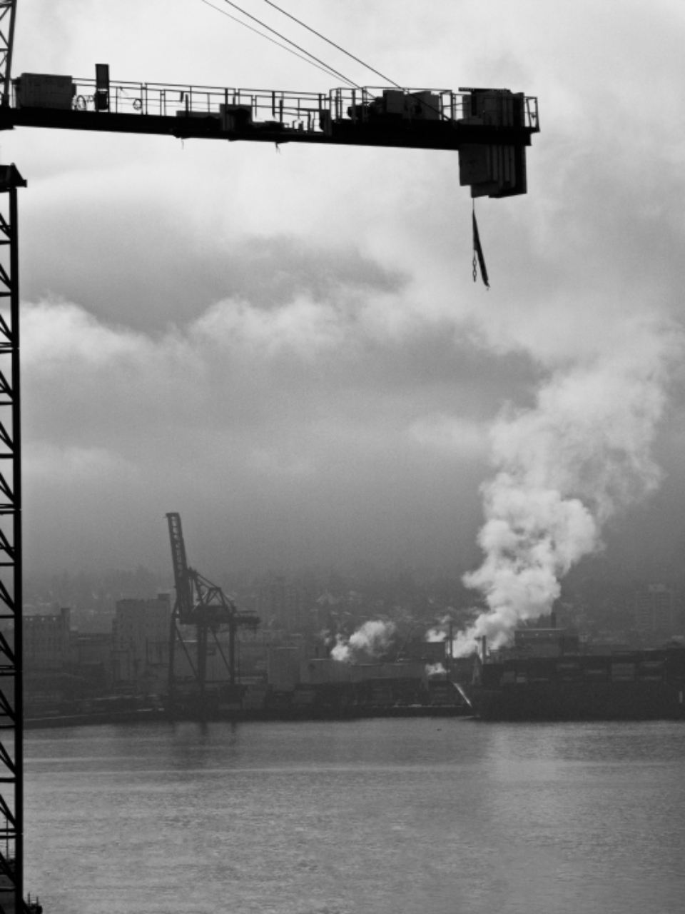 industrial crane city harbor buildings engineering construction clouds steam water black and white import freight dock