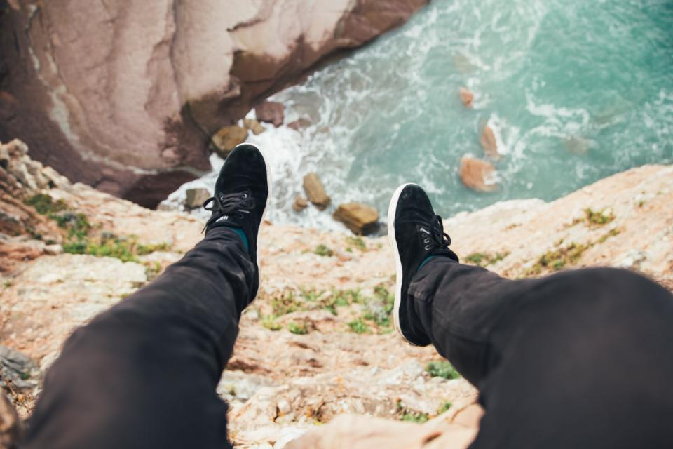 people legs shoe footwear travel adventure landscape outdoors sea ocean water coast seashore rocks cliff peak hill top view
