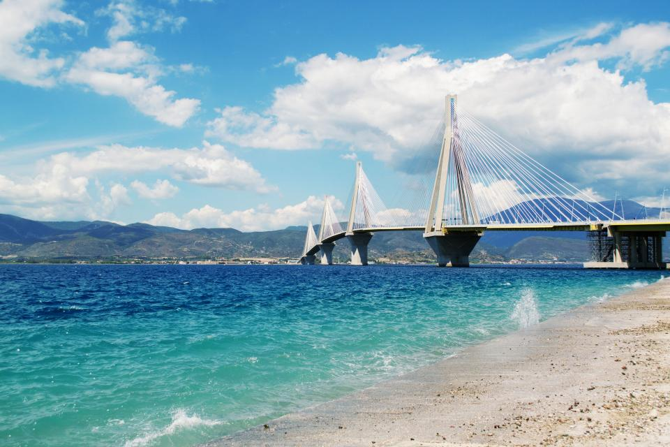 sea ocean blue water waves nature white sand beach seashore infrastructure bridge architecture travel outdoors mountain landscape view clouds sky