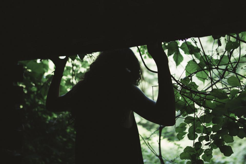 people woman dark shadow green leaves trees plants woods forest travel alone adventure