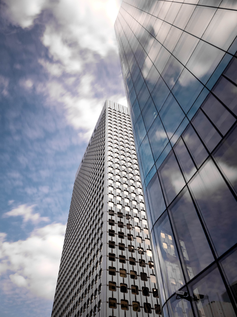 tall skyscrapers city buildings business offices windows architecture sunlight sky clouds downtown urban workplace