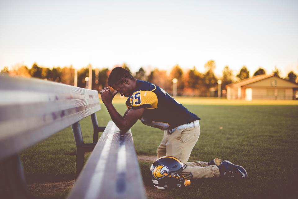 man people kneel praying bench helmet playground field blur athelete sport