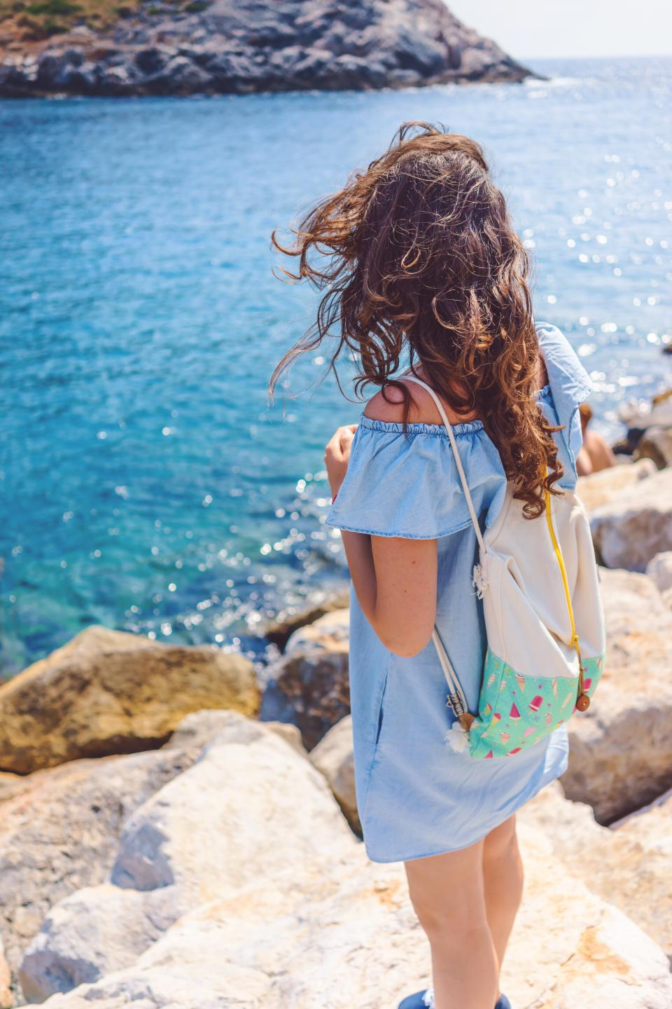 coast ocean sea water nature rocks blue girl dress bag hair wind people