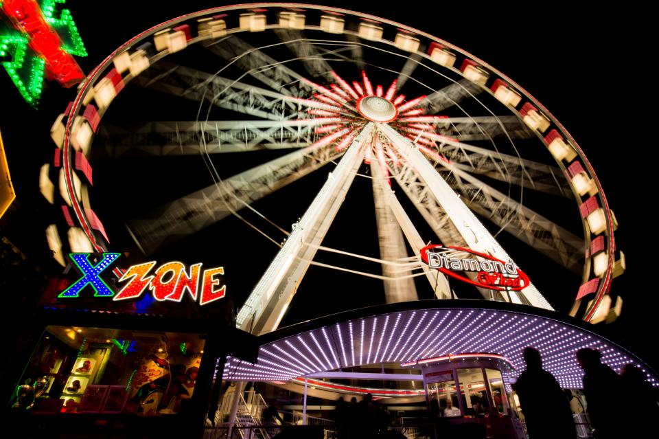 ferris wheel amusement park ride fair fun entertainment night dark people lights neon signs