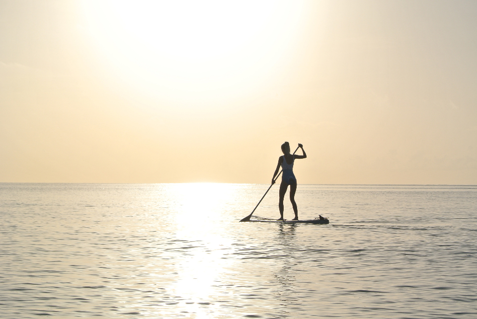 woman paddleboard sunset dusk evening sunrise calm gentle ocean sport travel
