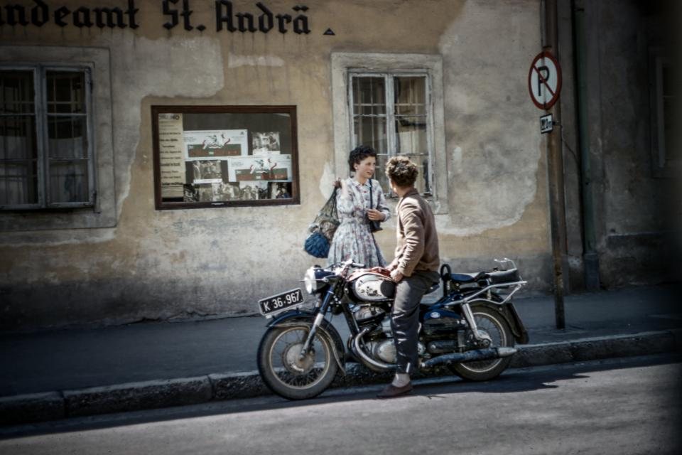people man woman motorcycle road old building store shop street vignette