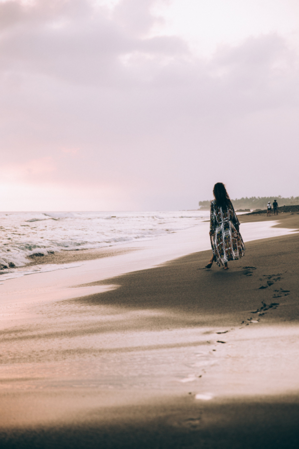 women beach sand ocean waves back view water shore coast walking person female sky footprints tide