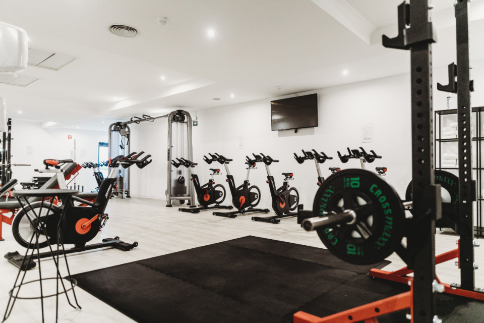 gym interior equipment workout fitness center empty weights bikes body building cardio bright tv white walls healthy