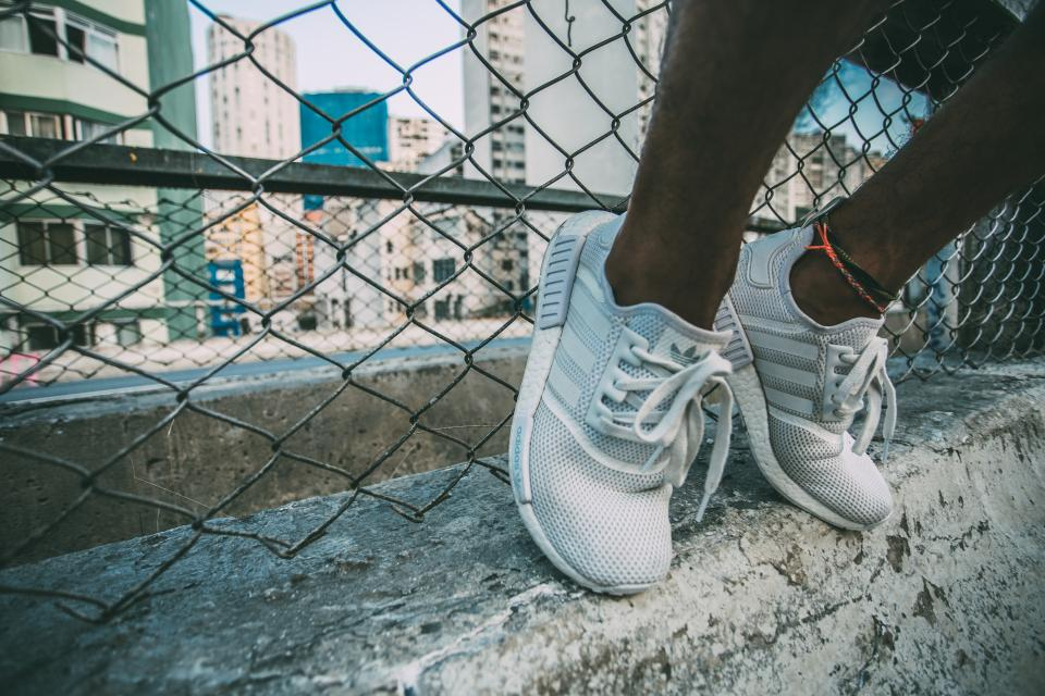 sneakers shoes feet concrete chainlink fence city urban people