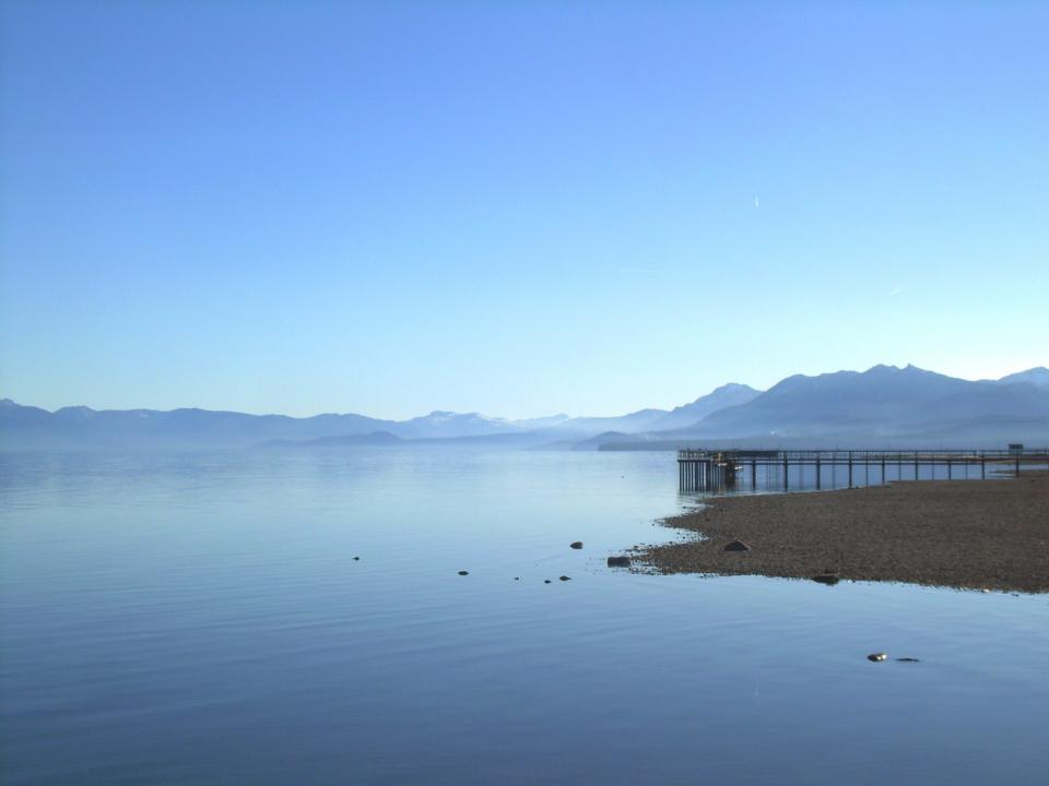 nature landscape mountains summit peaks shore beach sand water still calm bridge dock blue