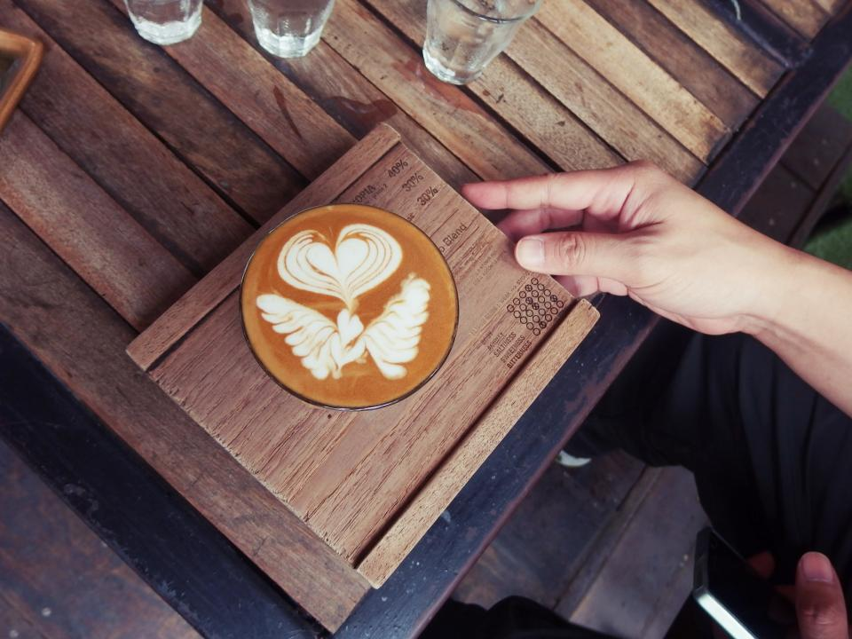 cafe latte espresso coffee art drink wooden table hand