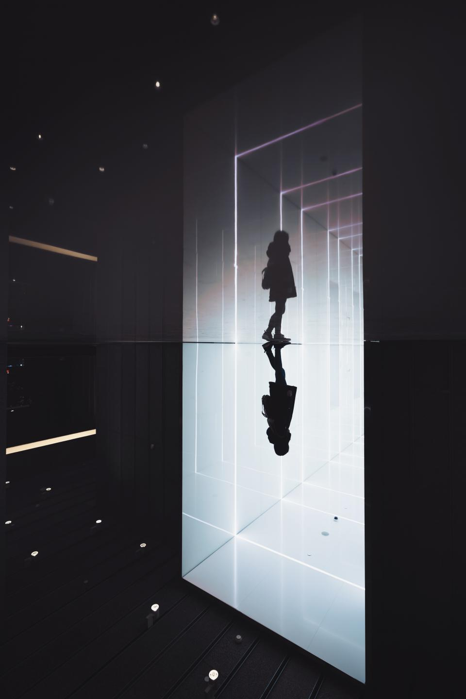 people woman alone walking building indoor dark silhouette floor reflection