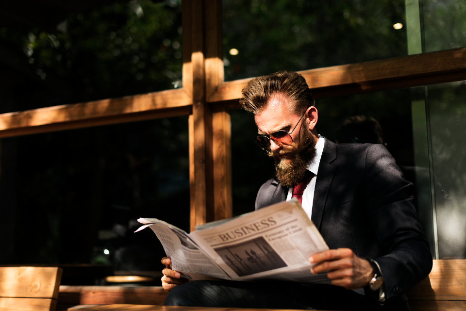 beard break business cafe coffee shop finance financial information man newspaper paper reading suit sunlight sunglasses corporate outdoors people