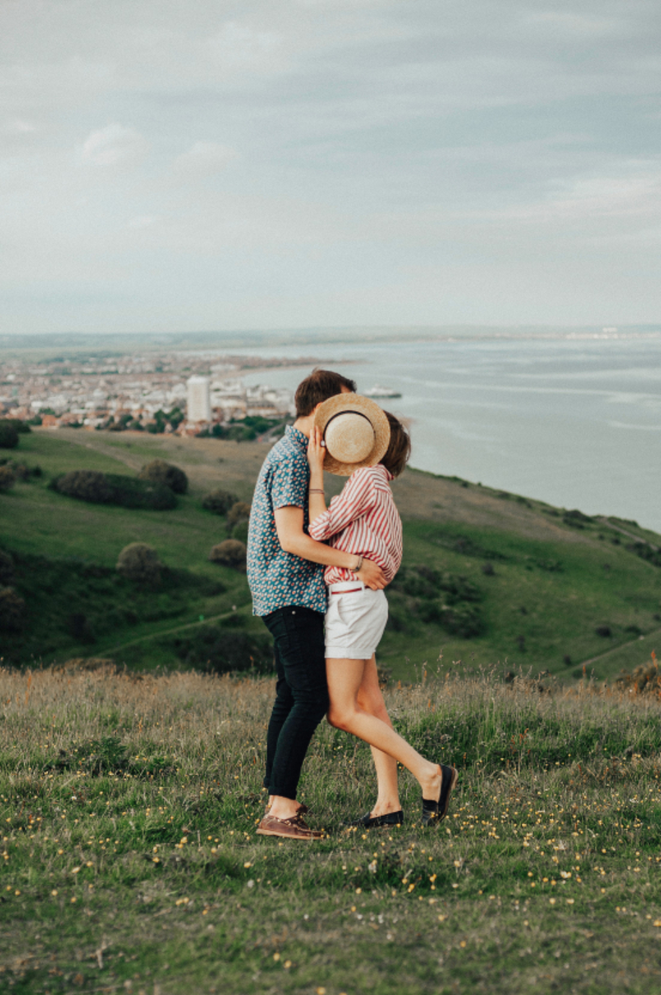 man woman kiss hat cover hidden landscape sea view sky clouds shorts male female girl