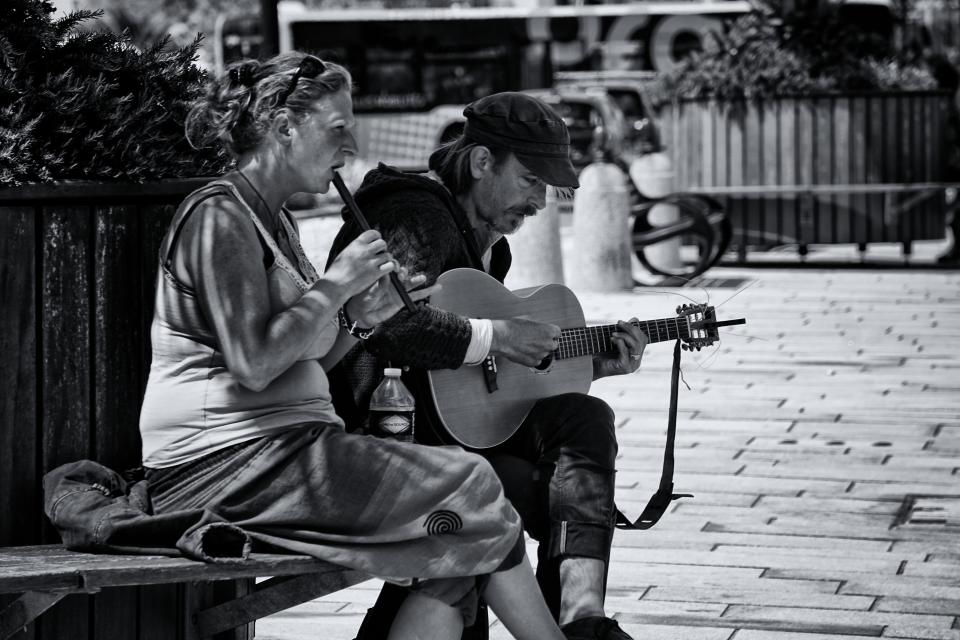 people man guy woman lady guitar flute bottle plastic bench garden plants music song singing couple lovers black and white