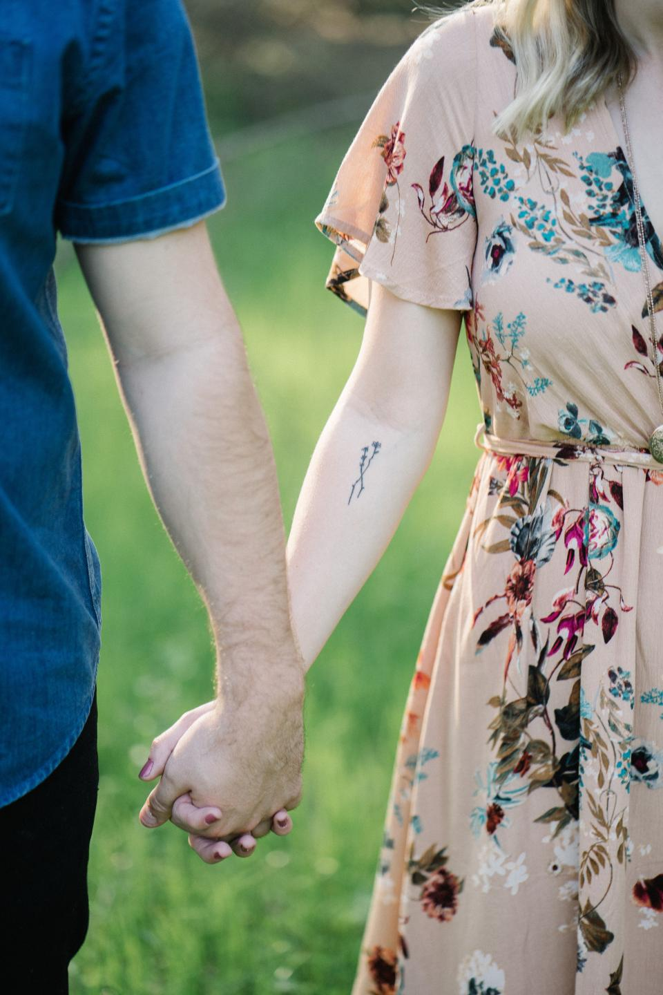 people couple holding hands man woman green grass blur