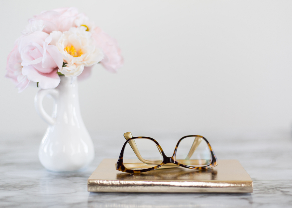 reading glasses table lenses fashion accessory close up eyeglasses object vase flowers minimal