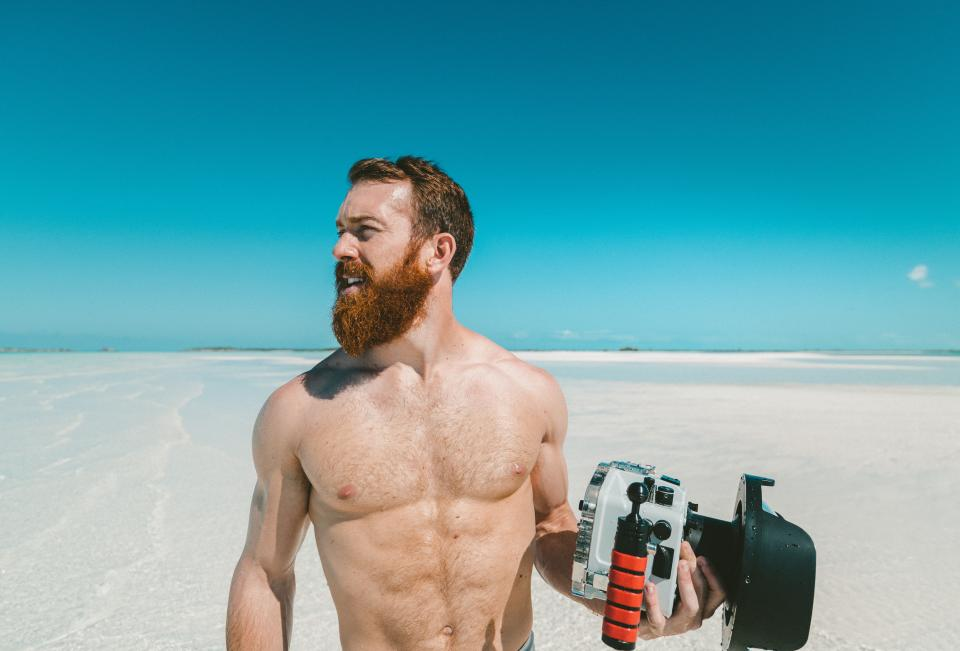 people man guy camera photo photographer muscle beach wave sands sea water sky clouds blue beard