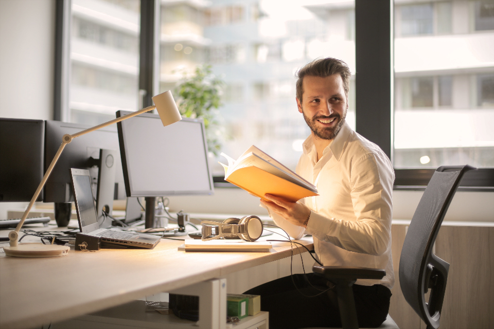 man smiling office work desk computer technology chair window yellow notepad documents light