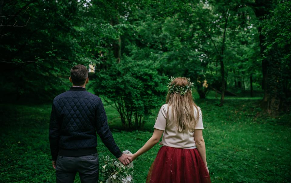 people man woman guy girl millennials holding hands flowers green grass outdoor adventure trees plant nature