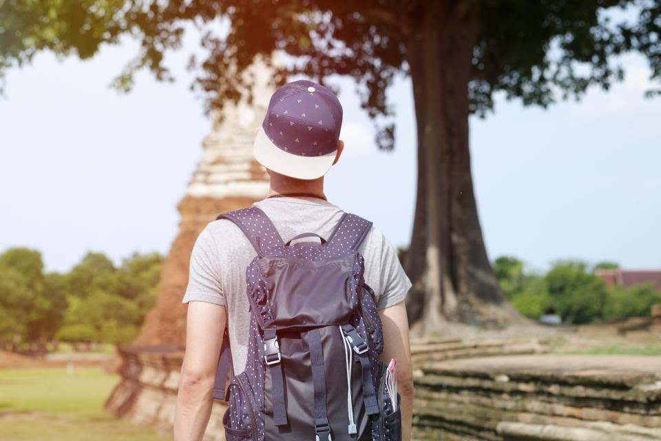 people man guy cap bag backpack walking alone reading book architecture building travel outdoor tree
