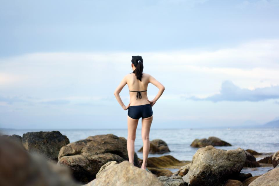 woman girl lady people back swimsuit style rocks shore water ocean sea sky clouds
