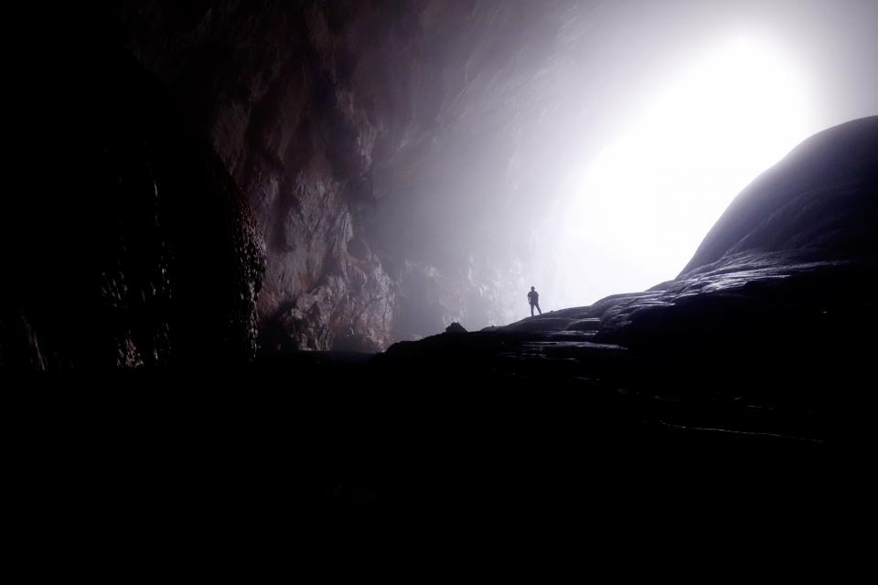nature cave underground shadows light rays guy man male people stand spelunking explore