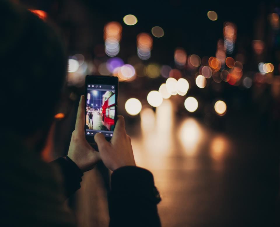 mobile phone lights capture photography hands touchscreen camera night blur bokeh people street road