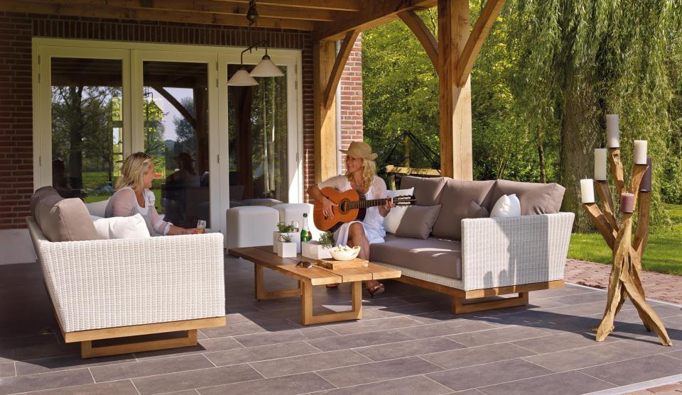 chair sofa couch wooden table outside lawn green grass nature fresh view floor tile vacation relax tableware flower trees house glass lamp guitar music people friend women talking smile happy sunny day candle
