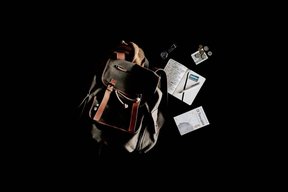 travel bag backpack notebook book pennies watch black
