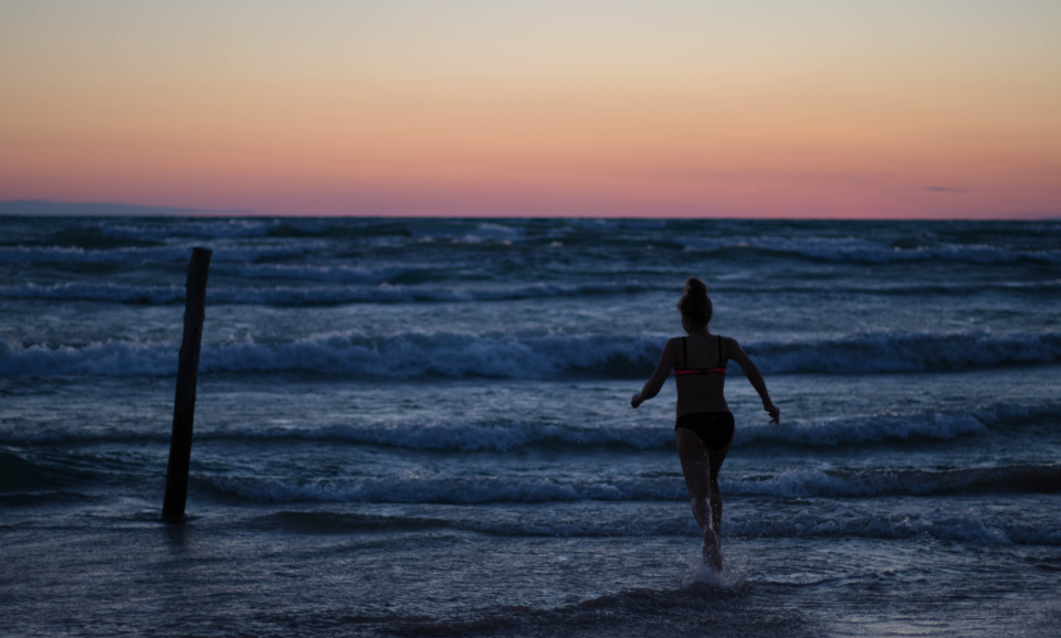 girl running beach ocean water wet fun play sunset dusk waves female