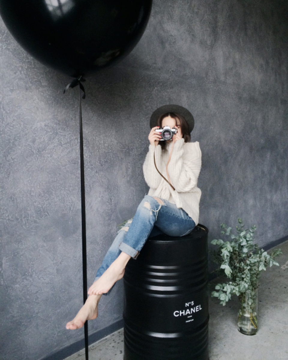 model photographer camera soot lens technology woman female girl people black barrel balloon pose hat jeans