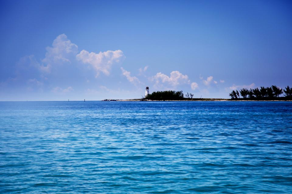 blue sky water sunshine summer coast shore lighthouse trees clouds landscape nature