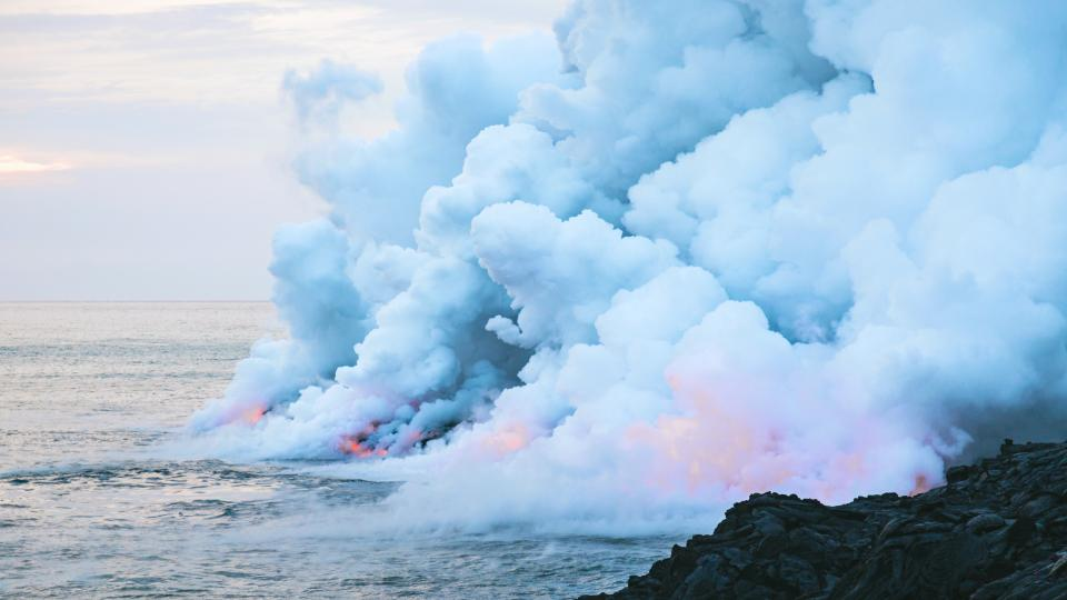 sea ocean blue water nature rocks coast clouds sky smoke volcanic landform