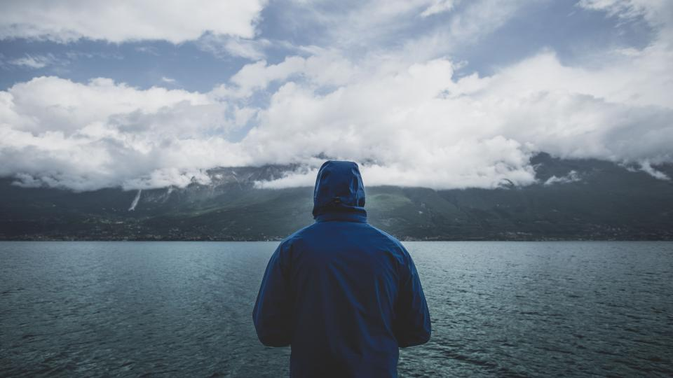 sea ocean water dark mountain highland view landscape nature people man alone hoodie cloudy sky clouds