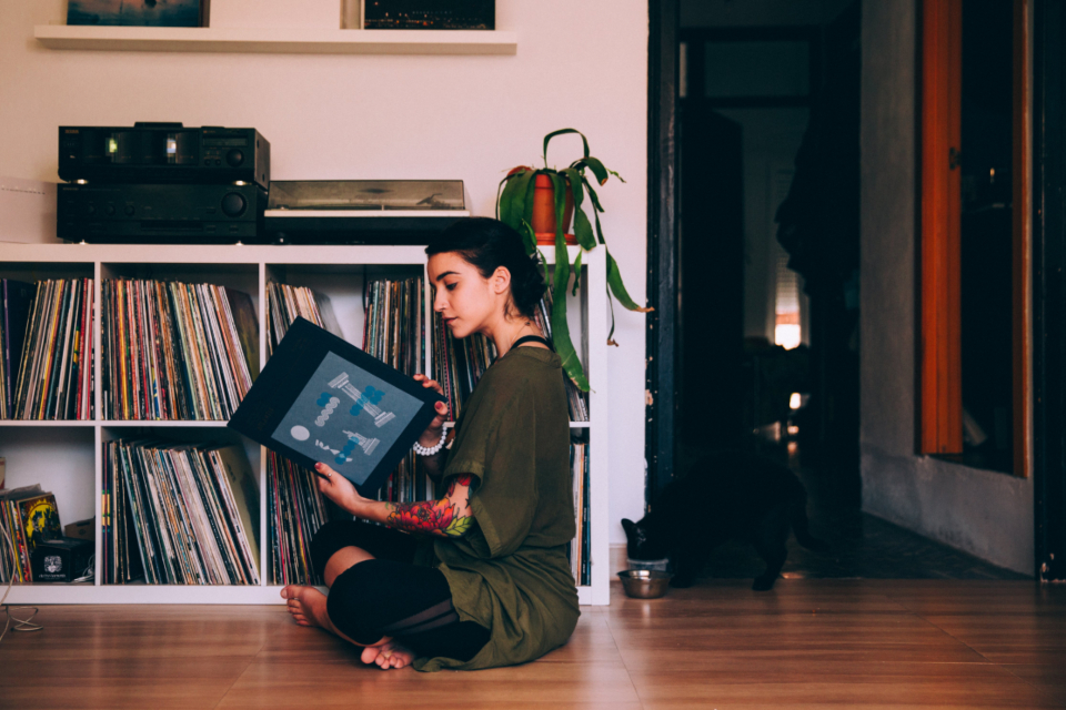 woman sitting reading records vinyl music home casual tattoo female person alone indoors living room living space