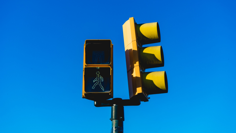 traffic light signal pedestrian walking crossing isolated sign signage blue sky city curb street