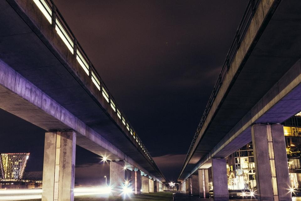 bridge lights city vehicle road cars traffic buildings infrastructure architecture urban travel tower