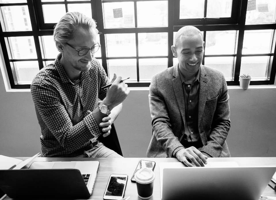 business meeting laptop brainstorming smiling colleague friend coffee phone digital device gadgets work office indoors cheerful communication computer connection discussion entrepreneur startup grayscale happy