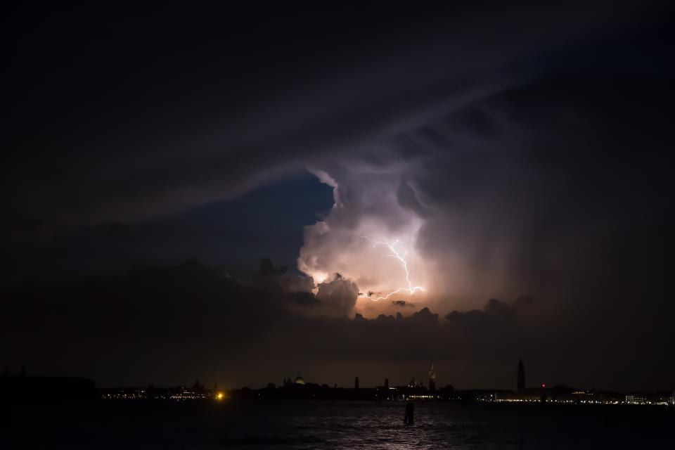 dark night clouds sky lightning storm sea ocean water lights