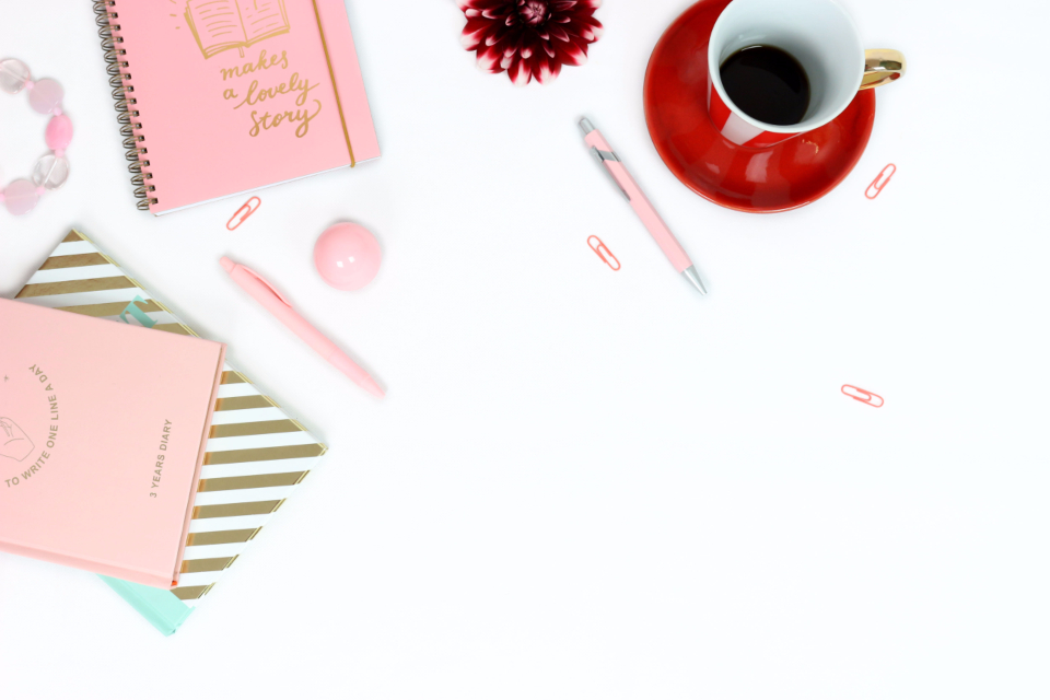 workplace desk feminine pink notebooks pens gold golden red red cup saucer dahlia jewlery paper clip white background turquoise cup of coffee pink pen pink diary diary stripes pastel color gold stripes
