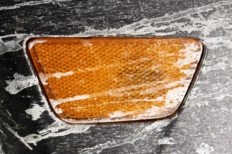 car blinker close up dirty salt unwashed crusted texture abstract messy macro orange automotive automobile transport